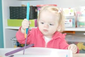 toddler grasping handful of craft sticks