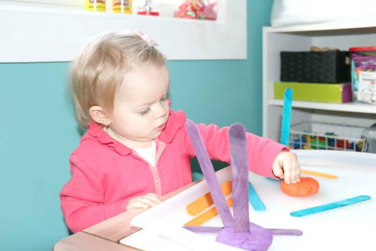 toddler pressing playdough onto tray