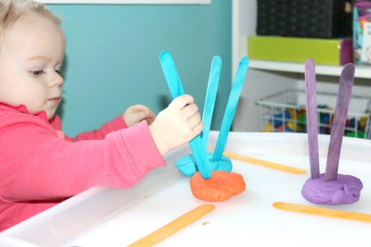 toddler pushing craft stick into playdough