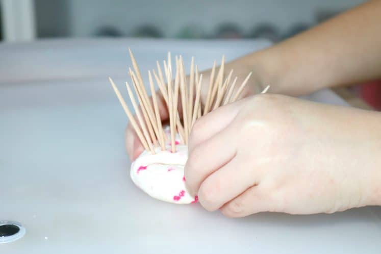 preschooler making hedgehog using toothpicks and playdough