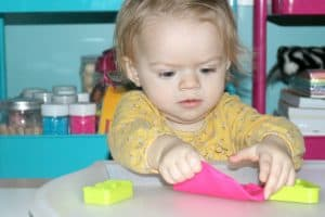 toddler exploring pink playdough