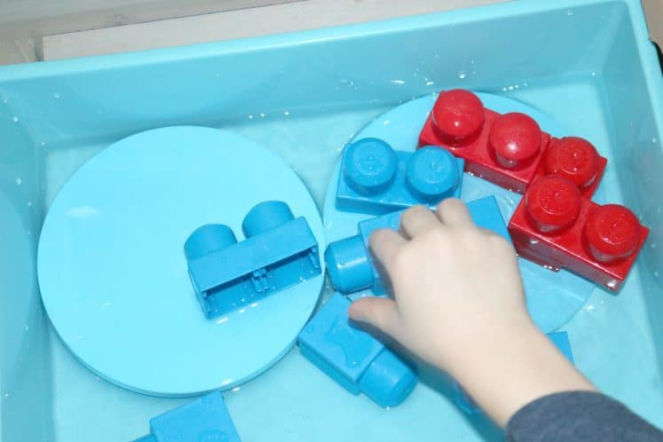 child stacking blocks in water