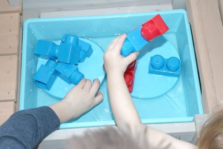 children balancing blocks in water