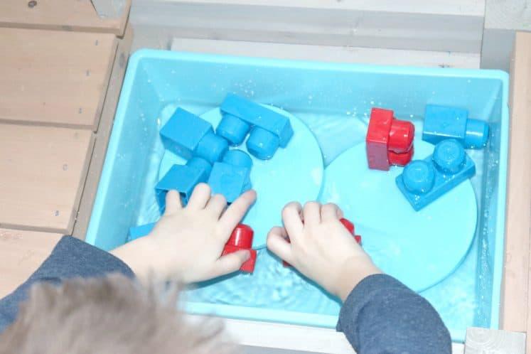 child building blocks in water sensory bin