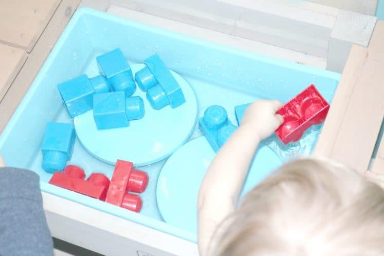child using plastic block to scoop water