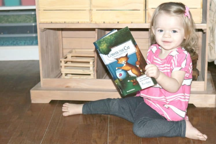 preschooler sitting on the floor with a book
