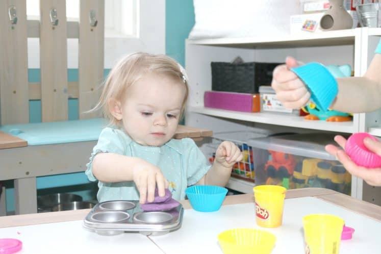 toddler pressing playdough into cupcake pan