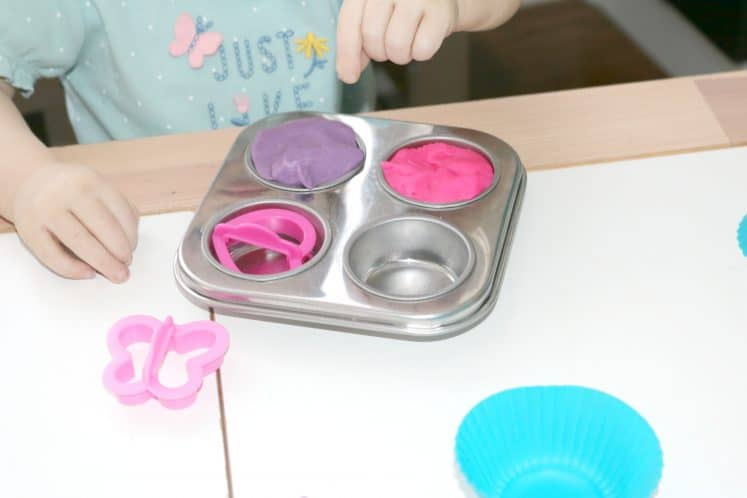 toddler making pretend cupcakes with different colors of playdough