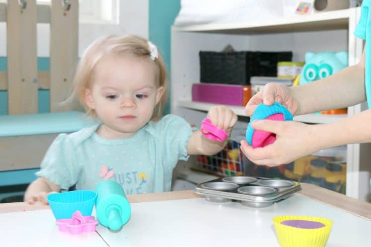toddler exploring cookie cutters and playdough