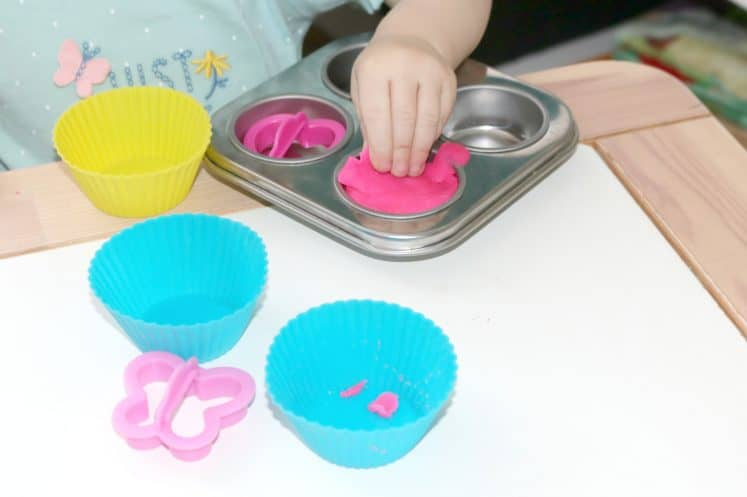 toddler making pretend cupcakes using playdough