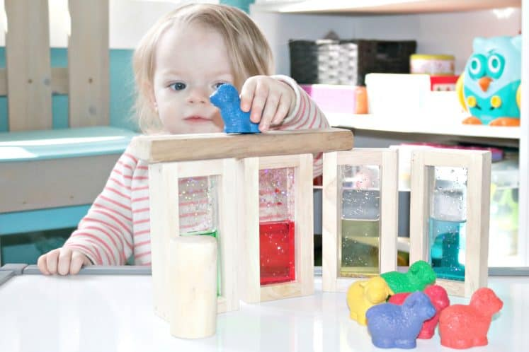 toddler playing with sheep manipulatives and wooden blocks