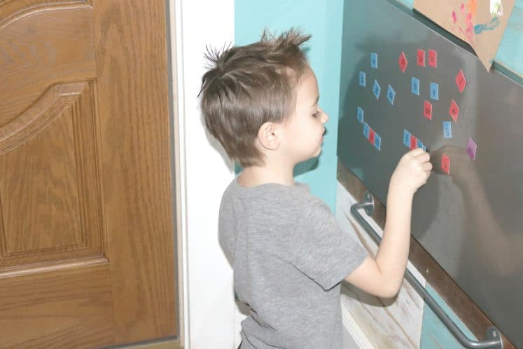 child spelling on magnet board with letter tiles