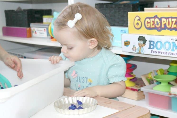 toddler looking at pretend treasure in sensory bin