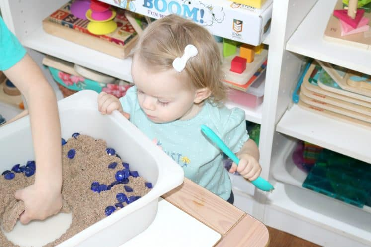 child using hands to dig for treasure in sensory bin