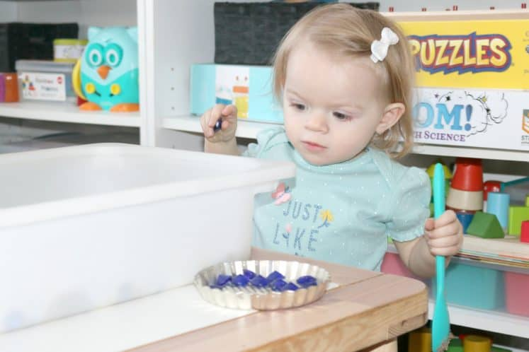 toddler holding small jewel in one hand and spoon in the other