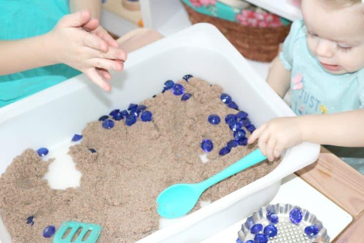 toddler digging for gems in sensory bin