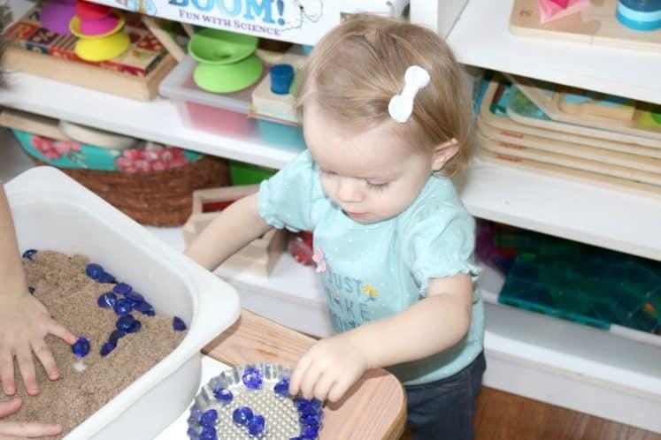 toddler putting small gems in metal pan