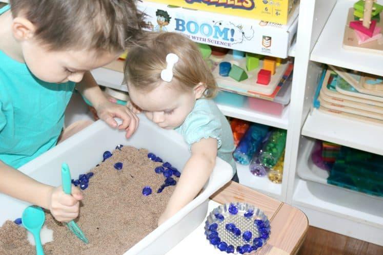 toddler digging for small gems in treasure hunt sensory bin