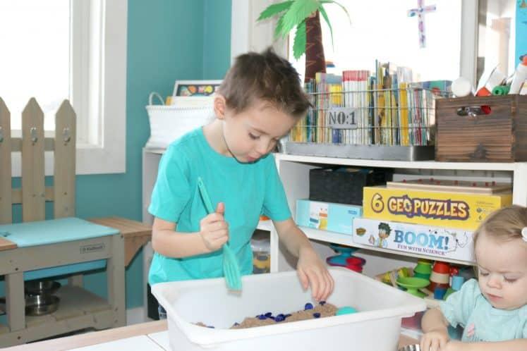 preschooler digging for jewels in sensory bin