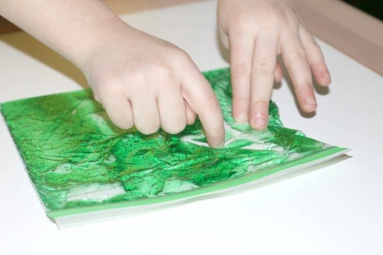 toddler using algae sensory bag to draw with fingers