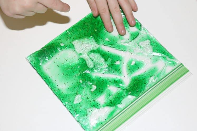 toddler pressing on algae sensory bag with hand