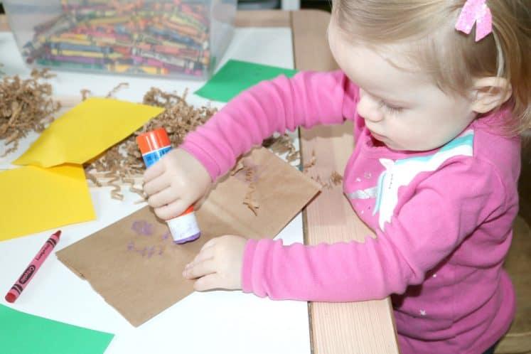 toddler putting glue on brown paper bag