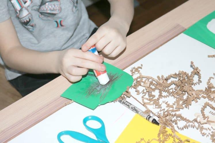 older child gluing crinkle paper onto bird nest process art