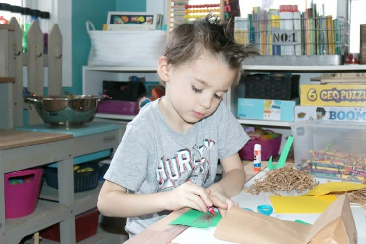 child coloring on green cardstock to make bird nest craft