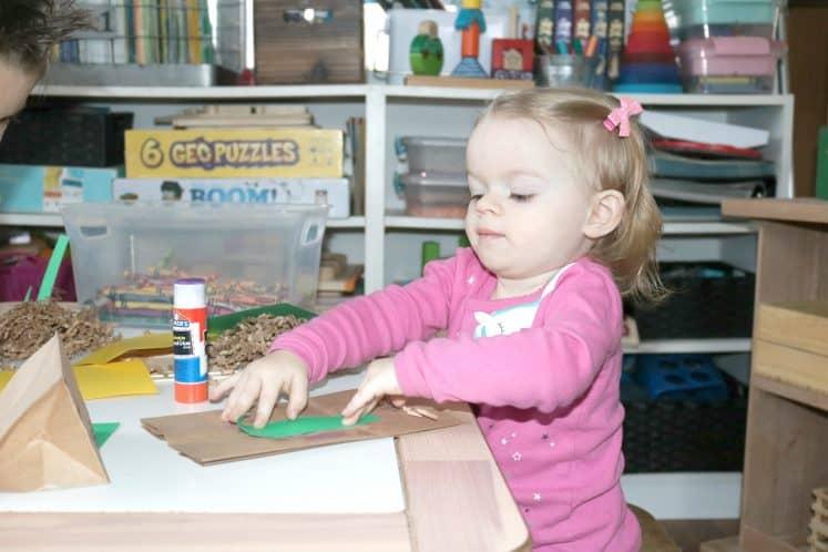 toddler gluing cardstock onto brown paper bag