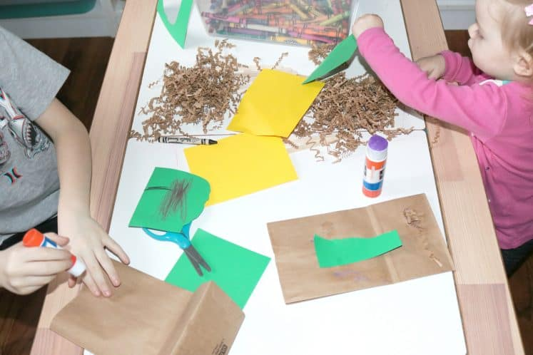 toddler and first grader making bird nest process art next to one another