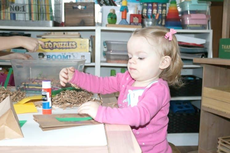 toddler making bird nest craft using cardstock and paper bag