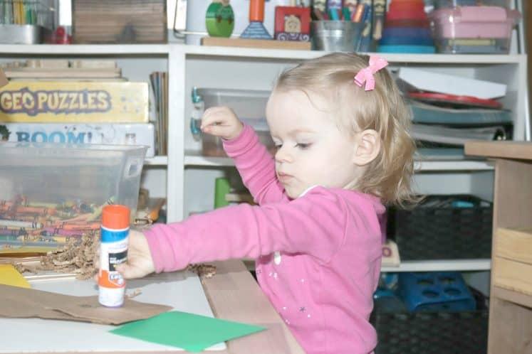 toddler gluing bird nest craft