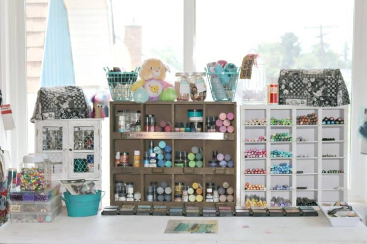 craft workspace with paints, inks and markers in wooden organizers