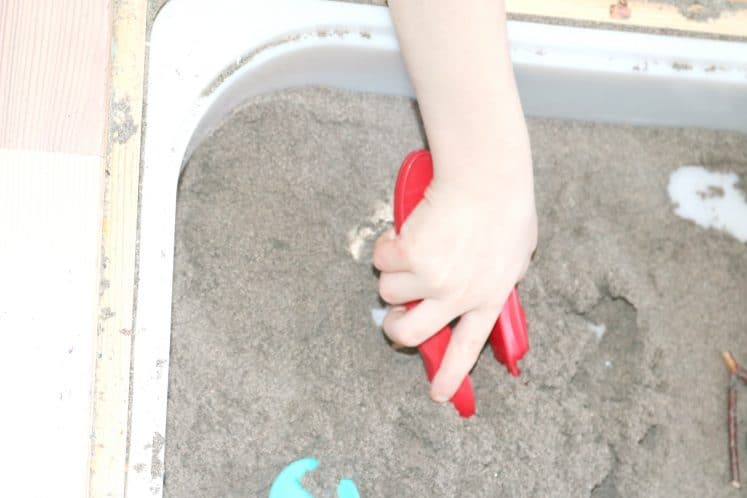child using tweezers to dig for pretend bird food in sensory bin