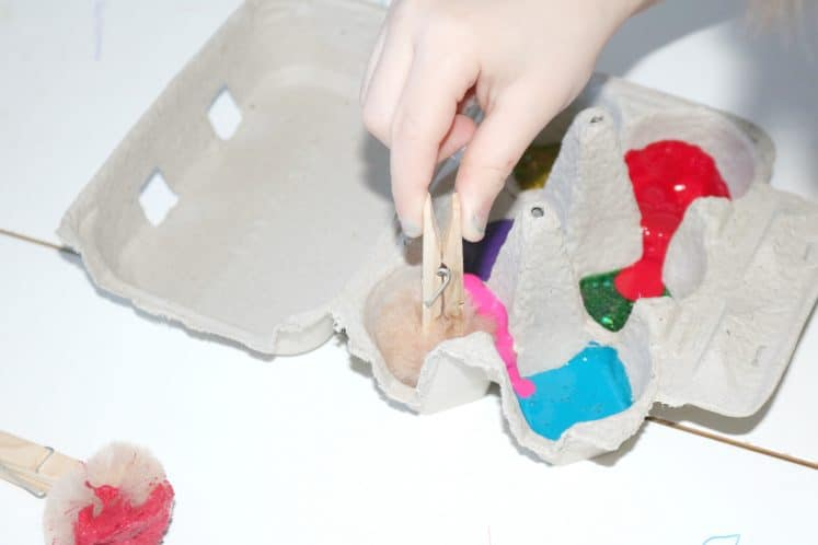 preschool dipping pompom into paint