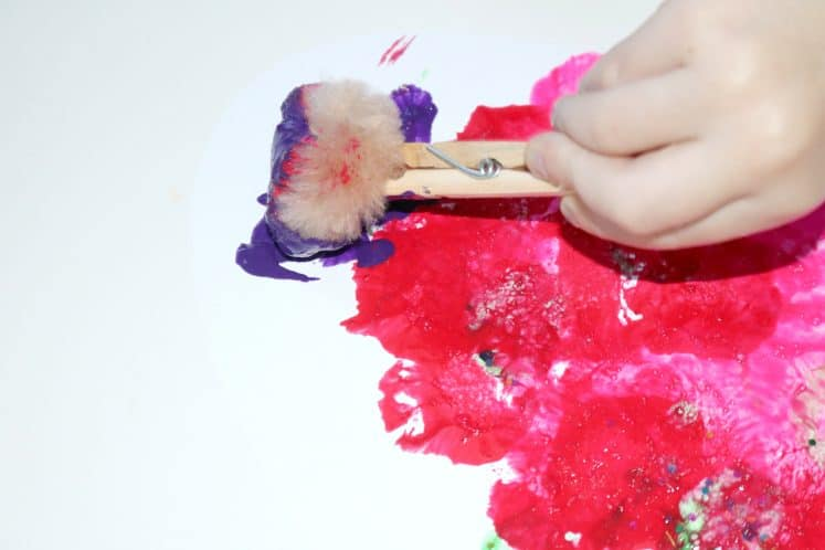 preschooler using clothespin with pompom to paint