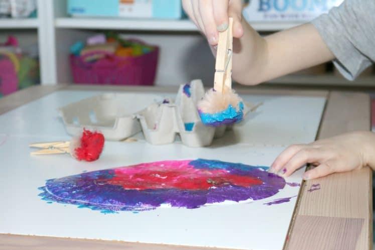 preschooler painting cardstock egg using pompom