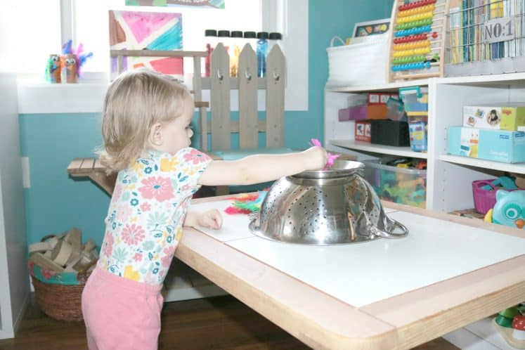 toddler putting a pink feather into an upside down strainer