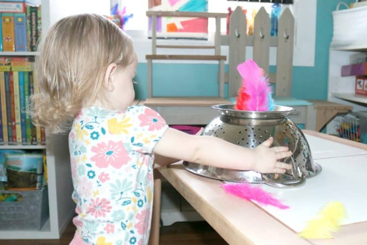 toddler holding upside down strainer with colored feathers sticking out
