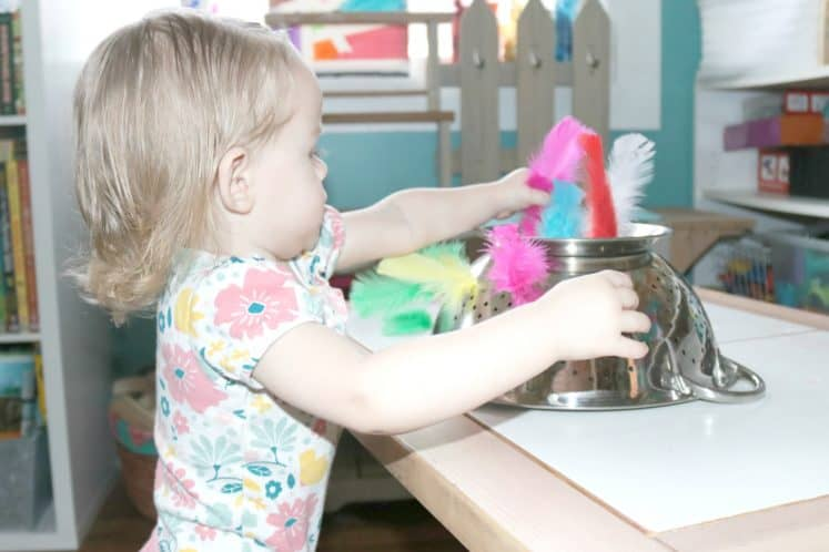 toddler putting colored feathers into an upside down strainer