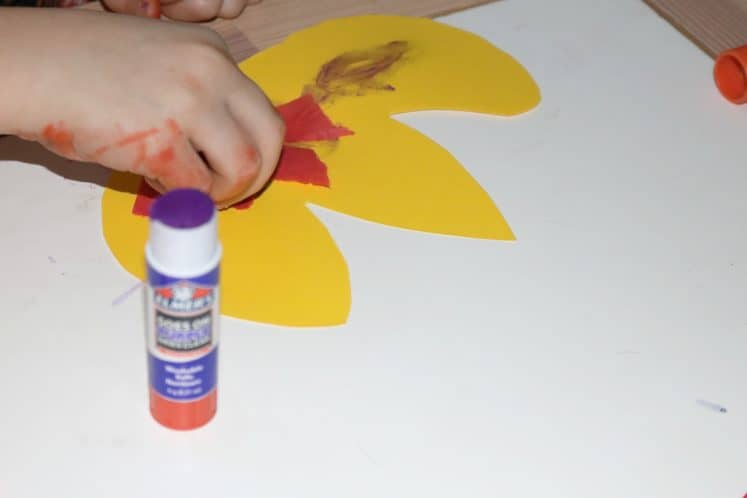 child gluing tissue paper onto yellow paper flame