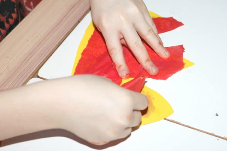 child adding red tissue paper to yellow paper flame