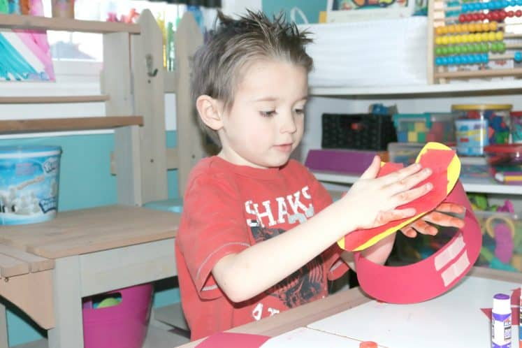 child attaching paper flame to headband