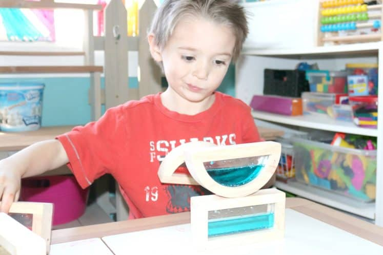 child stacking water-filled play blocks