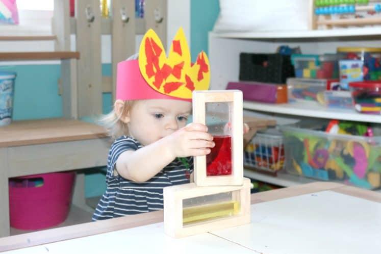 toddler wearing raining fire headband and stacking water-filled blocks