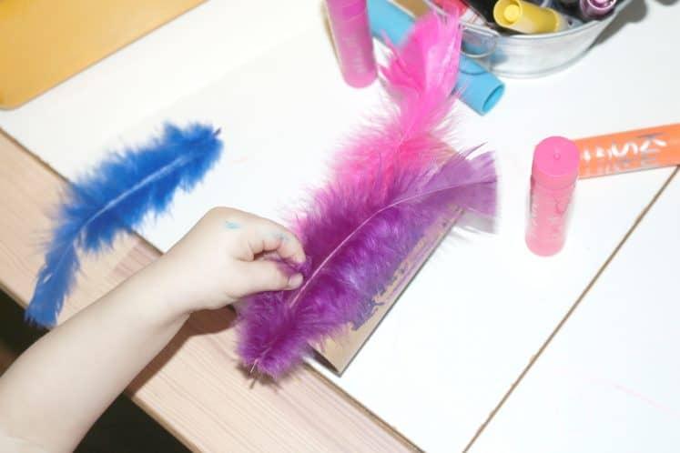 preschooler adding feathers to cardboard roll