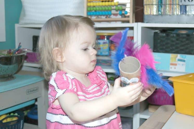 preschooler holding cardboard roll bird craft