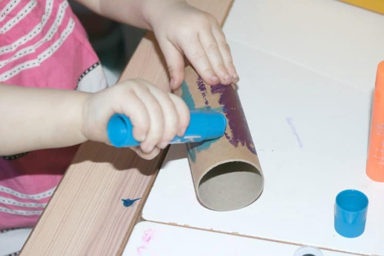 preschooler painting with paint stick