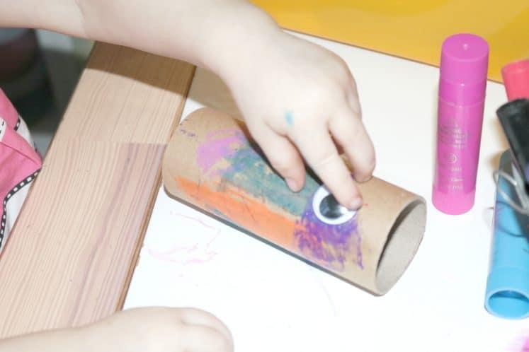 preschooler gluing wiggle eyes to bird craft