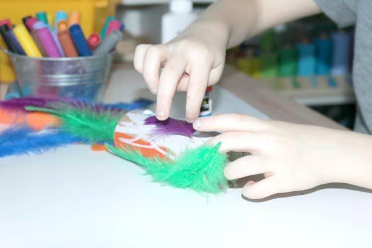 preschooler gluing feather on bird craft